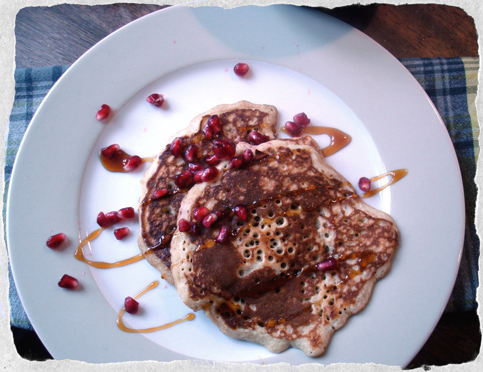 Banana pancakes with syrup and pomegranates